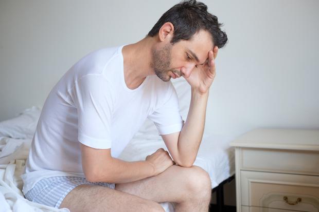 sad man sitting on his bed